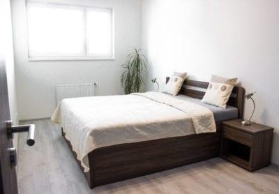 bílá ložnice s tmavou postelí